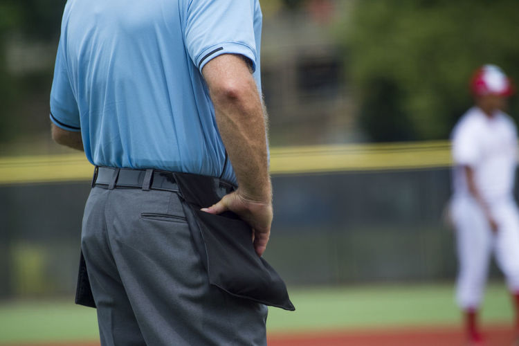 Midsection of referee standing on field