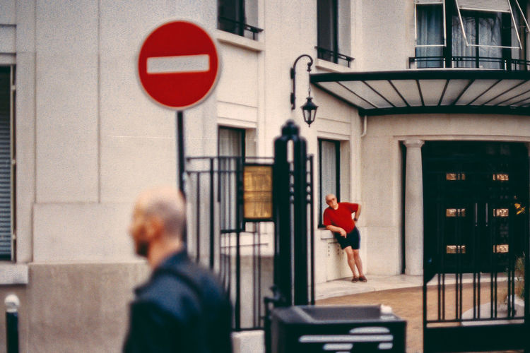 La retraite 35mm Film Chill City Communication Day Focus On Foreground Incidental People Lifestyles Men People Photography Real People Red Road Sign Sign Street This Is Aging