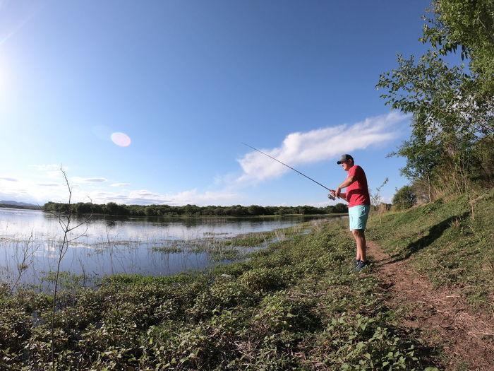 Full length of man fishing on lake against sky