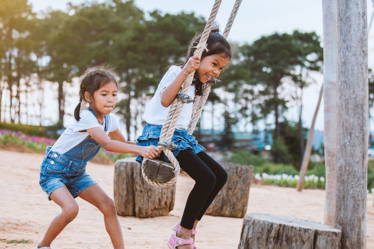Side view of girl pushing sister on swing at playground