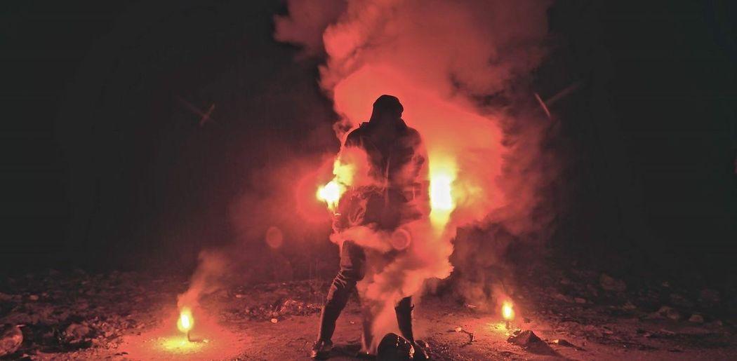 Person wearing gas mask holding smoke bombs