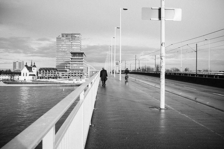 People walking on bridge over rhine river against sky