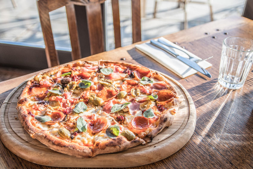 The best pizza you will never taste! Authentic Board Cafe Close Up Crispy Crust Cutting Food And Drink Homemade Hospitality Hot Pizza Place Setting Place Settings Real Italian Real Pizza Restaurant Service Sunny Day Table Table Setting Takeaway Tasty Toppings Wooden