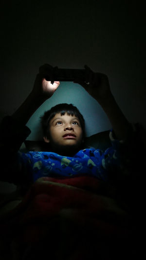 Boy Using Phone While Lying In Darkroom