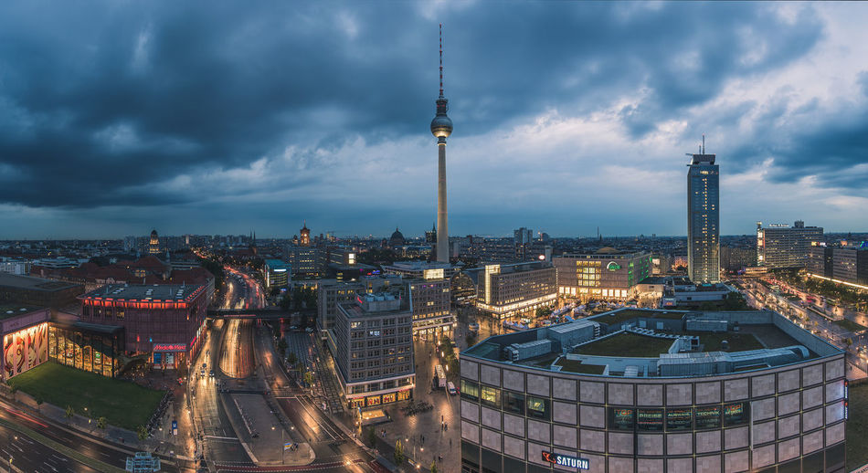Fernsehturm In Illuminated Cityscape Against Cloudy Sky At Dusk