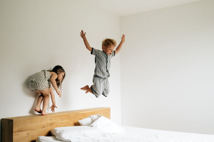 Siblings playing on bed jumping on the mattress on a morning daylight