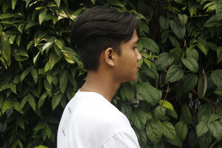 Side view of young man standing by plants