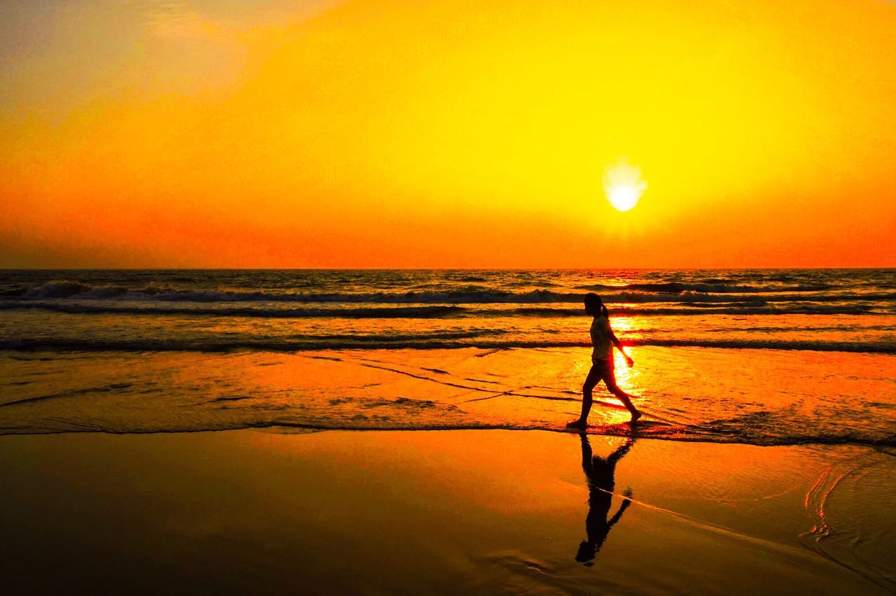 sunset, sea, beauty in nature, nature, scenics, orange color, real people, silhouette, water, sun, one person, leisure activity, beach, standing, sky, outdoors, full length, horizon over water, lifestyles, wave, day, people