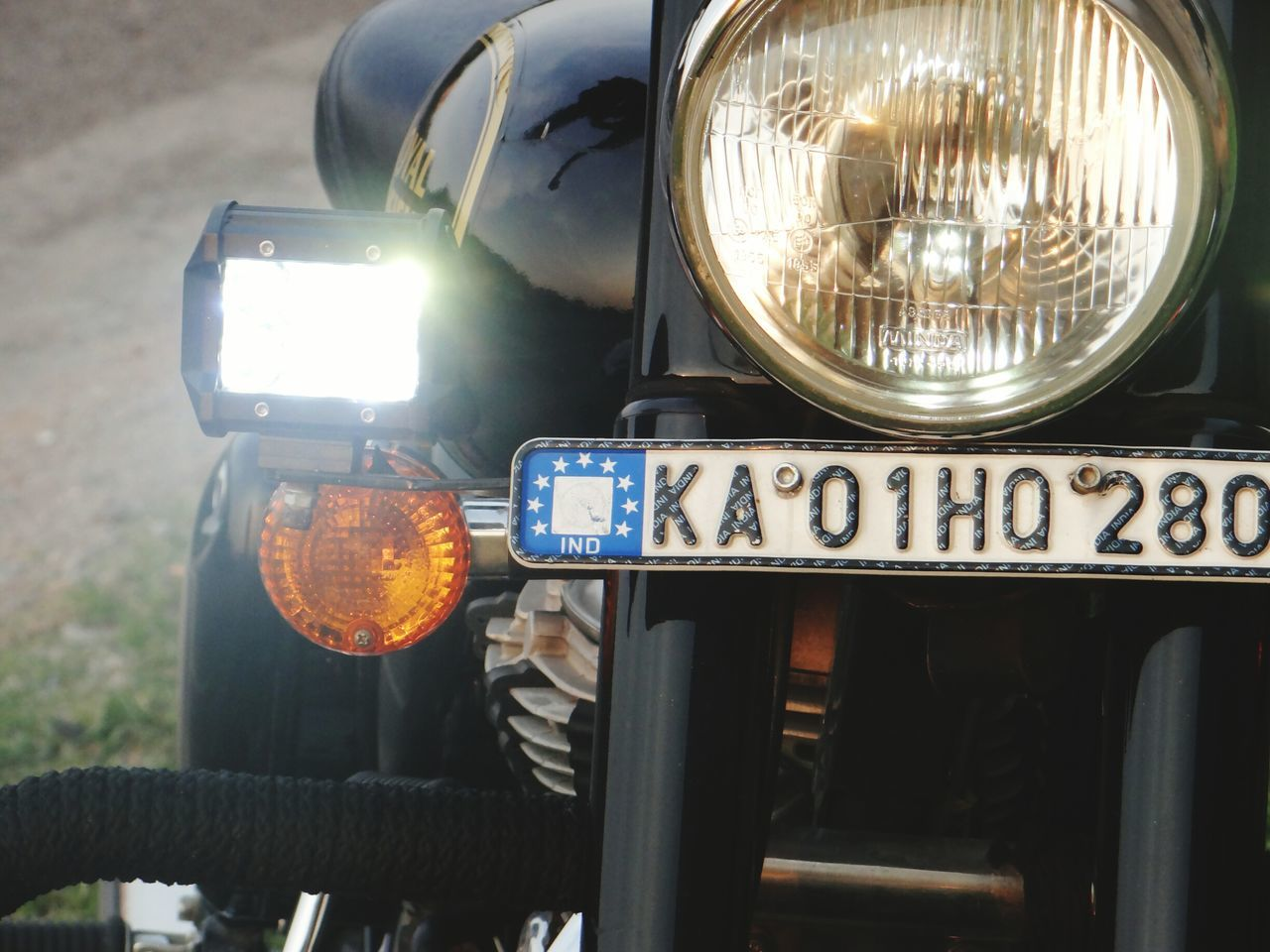 headlight, transportation, outdoors, text, land vehicle, day, no people, mode of transport, close-up, focus on foreground, illuminated