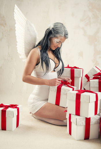 Young woman as angel with heap of gift boxes posing indoors Celebration Christmas Event Holiday Makeup Myth Presents Woman Angel Angel Wings Brunette Caucasian Conceptual Gift Boxes Gifts Indoors  Indoors  Long Hair One Person Real People Red Ribbon Sexygirl Studio Shot Young Adult Young Women