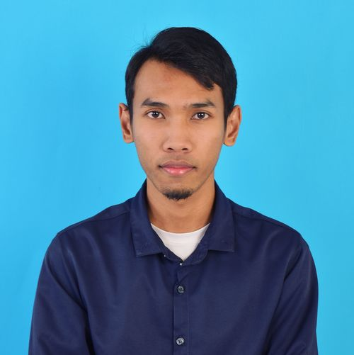 Portrait of young man against blue background