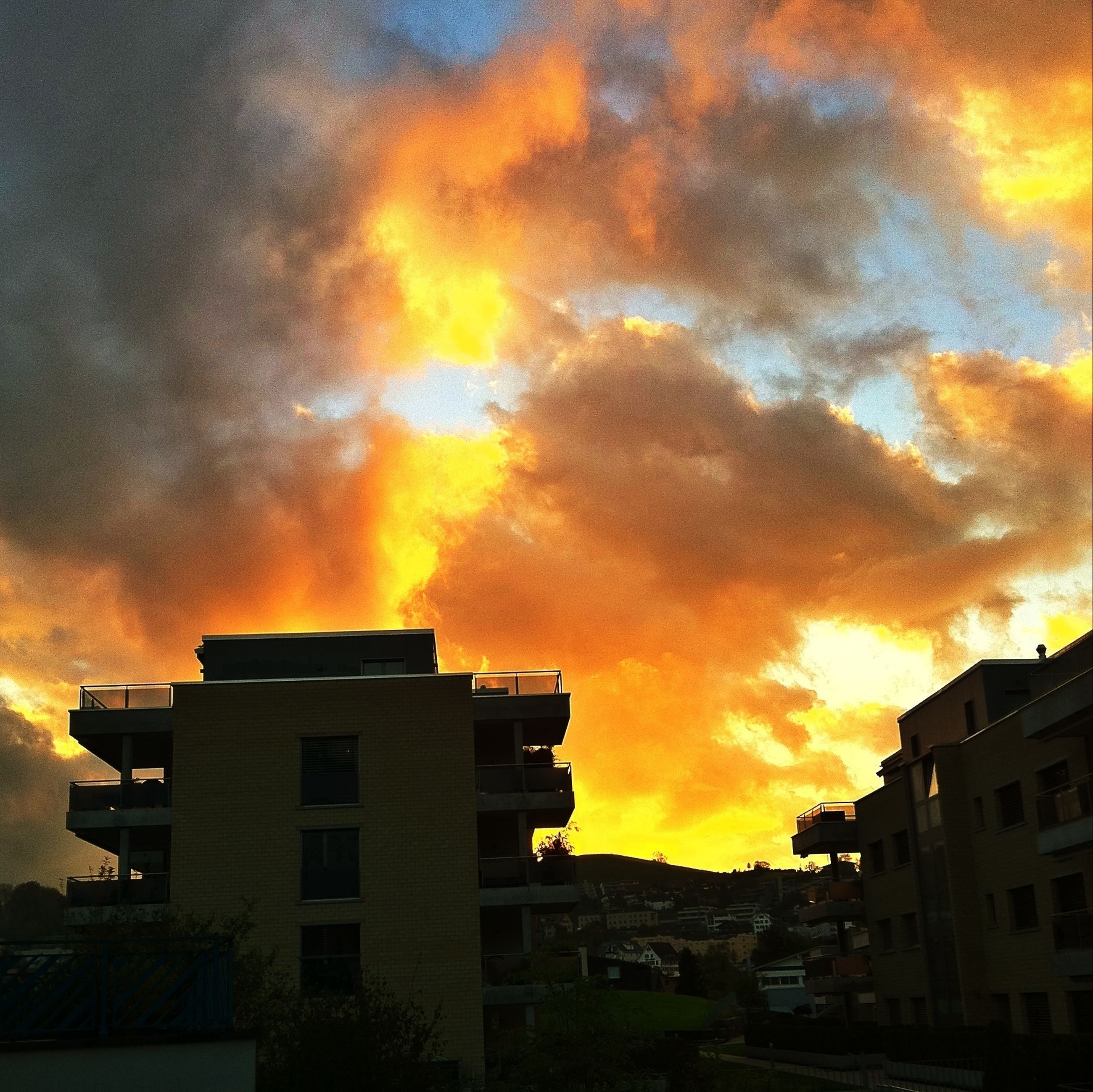 sunset, building exterior, architecture, built structure, sky, cloud - sky, orange color, cloudy, low angle view, city, residential building, dramatic sky, residential structure, building, house, weather, cloud, overcast, silhouette, outdoors