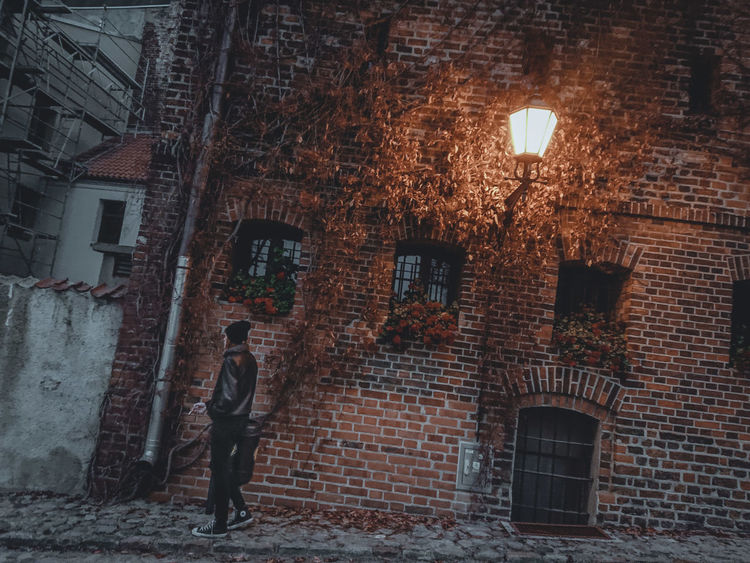 Aslant November Evening Toruń Lantern Medieval Brick Wall Standing Warm Clothing Outdoors Illuminated Night Built Structure Architecture The Week on EyeEm A New Perspective On Life