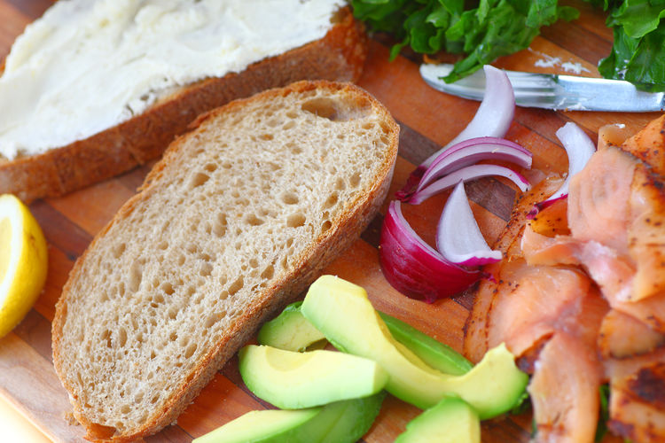 Making a smoked salmon sandwich with avocado from overhead Homemade Food Lunch Meal Natural Light Smoked Salmon  Textures Artisan Bread Avocado Close-up Delicious Fish Food Healthy Eating Indoors  Lemon Making Sandwich No People Ready-to-eat Red Onion Serving Size Snack Studio Shot Supper