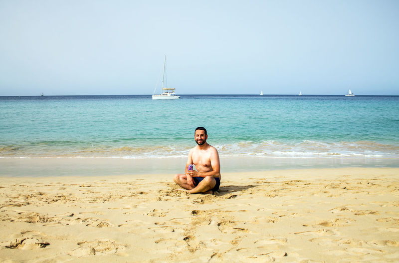 Portrait of shirtless mid adult man sitting on beach against clear sky during sunny day
