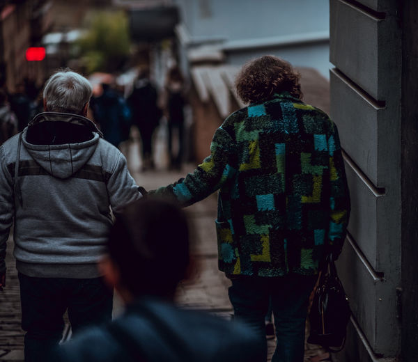 Rear view of couple holding hands while moving down on steps