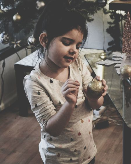 Close-Up Of Smiling Girl Holding Bauble At Home