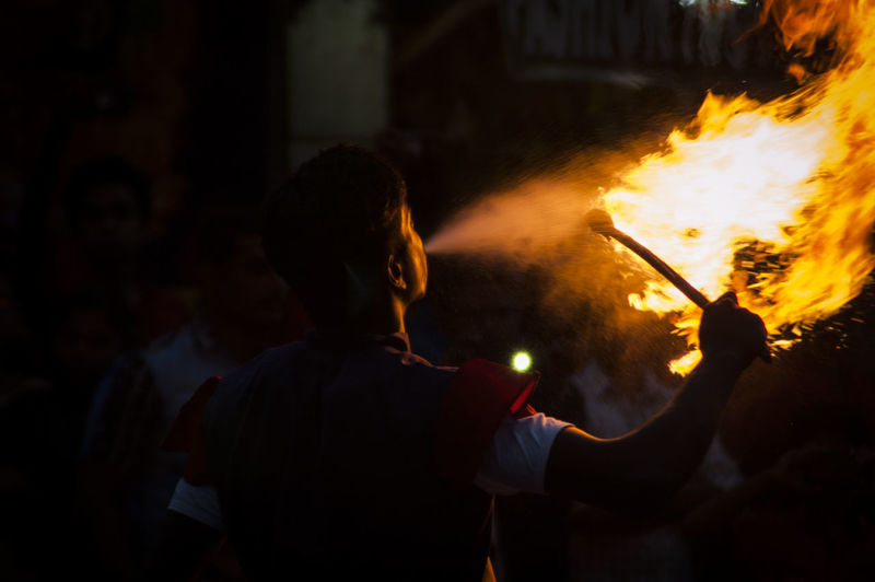 Rear view of man performing fire arts at night
