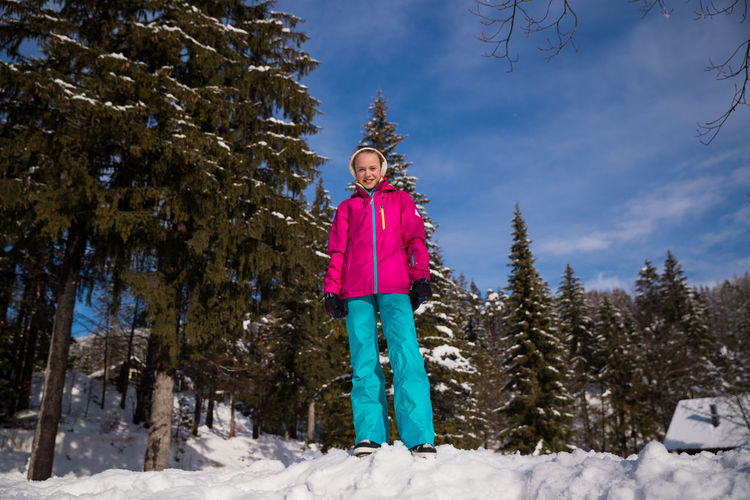 Portrait of child standing on snow covered land