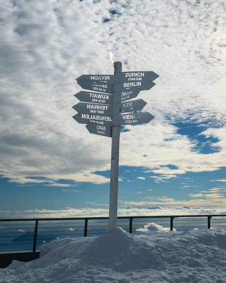 Information sign on snow covered road against sky
