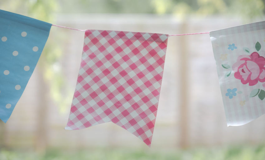 Close-up of buntings hanging against blurred background