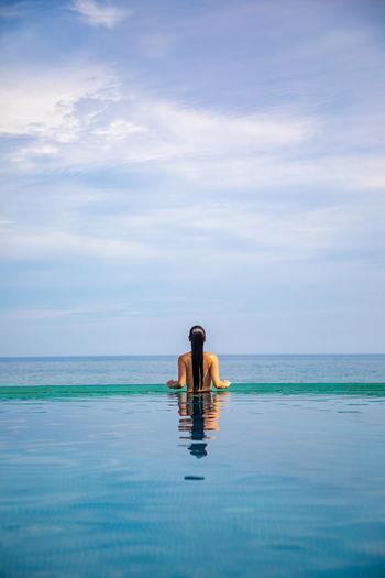 Rear view of woman in infinity pool against sky