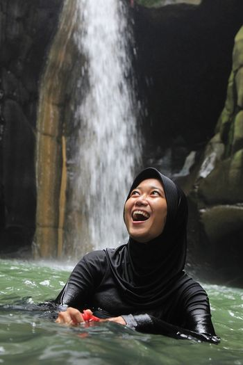 Portrait of smiling young woman in water