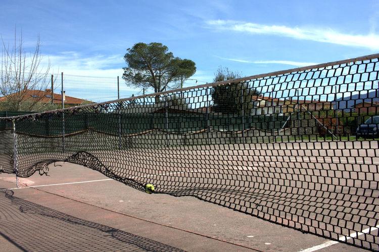 Net On Tennis Court Against Sky