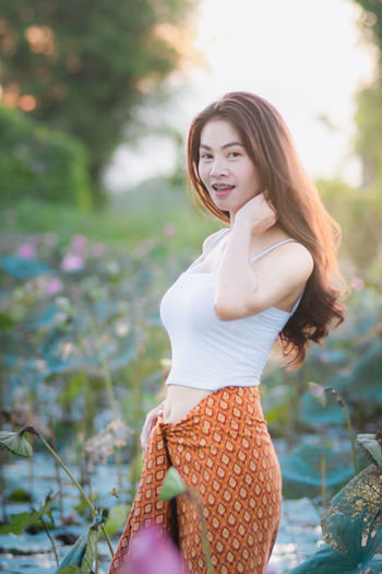 Young Women One Person Young Adult Three Quarter Length Beautiful Woman Beauty Women Real People Focus On Foreground Leisure Activity Hairstyle Adult Day Long Hair Smiling Standing Lifestyles Brown Hair Hair Fashion Outdoors