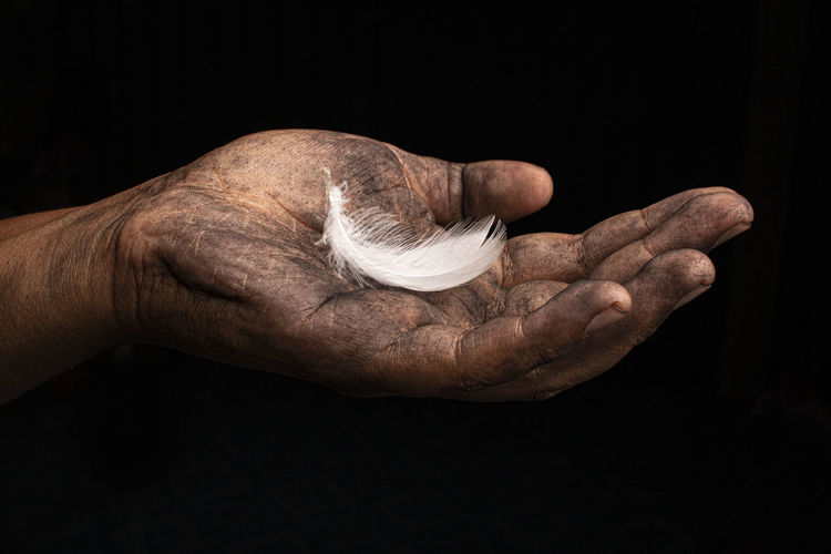 Close-up of man hand against black background