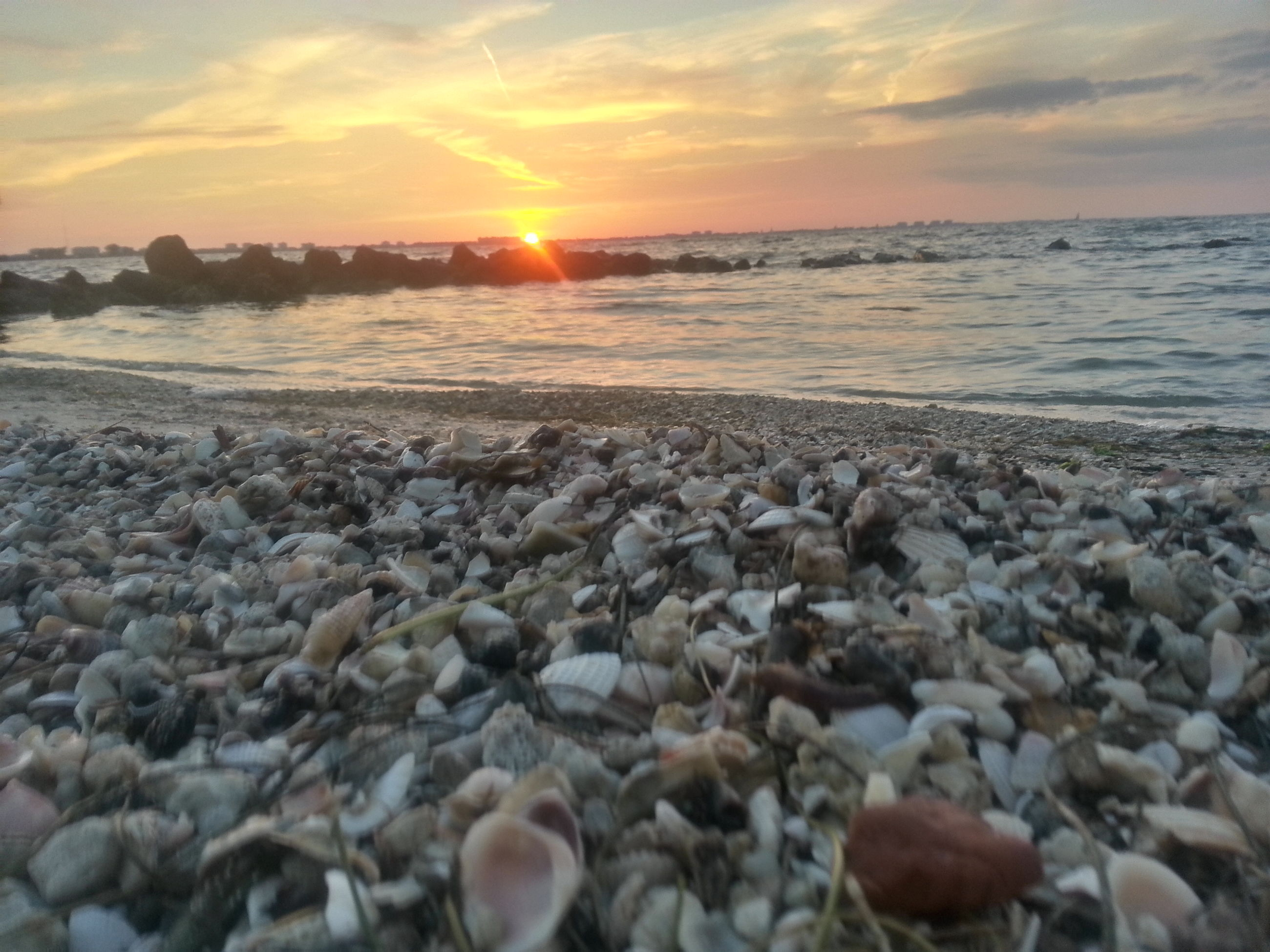sunset, sea, beach, water, sky, scenics, tranquil scene, beauty in nature, horizon over water, tranquility, shore, sun, nature, cloud - sky, orange color, idyllic, stone - object, rock - object, reflection, pebble