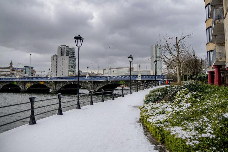 Bridge over snow covered city against sky