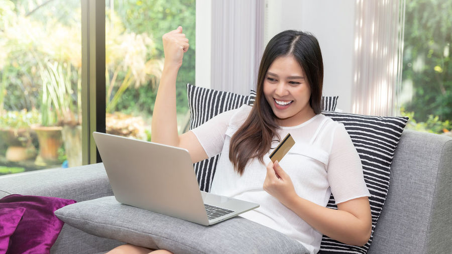 Smiling young woman using mobile phone while sitting at home