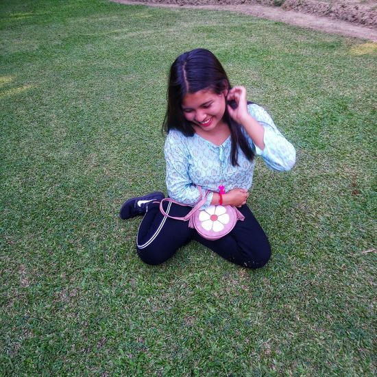 High angle view of smiling woman sitting on grass