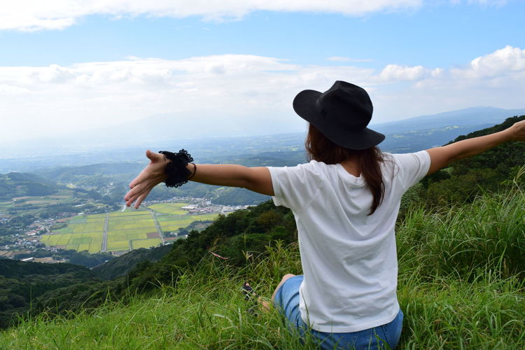 Rear View Of Woman With Arms Outstretched On Grassy Hill Against Cloudy Sky