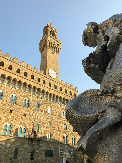 part of the modern giant sculpture called Big Clay in front of Palazzo Vecchio in Florence Artist Florence, Italy Piazza Della Signoria Firenze Urs Fischer  Ancient Architecture Art Big Clay Blue Building Exterior Built Structure Clear Sky Clock Tower History Low Angle View Modern Art No People Outdoors Palazzo Vecchio Sculpture Sky Sunlight Travel Destinations