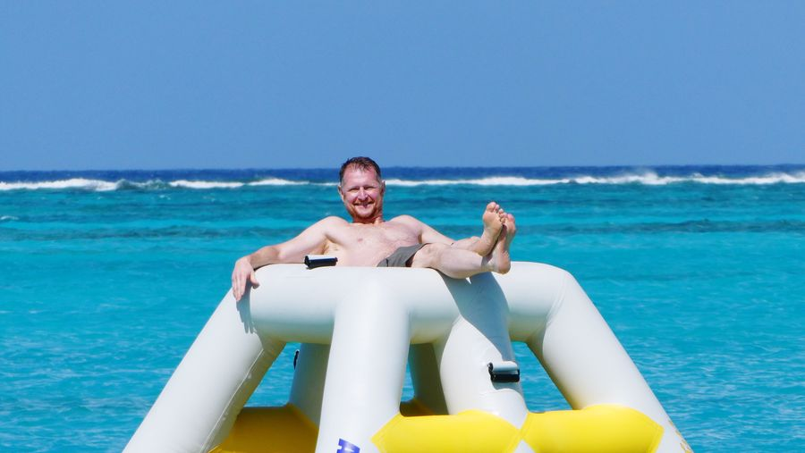 Portrait of shirtless man relaxing in inflatable against sea