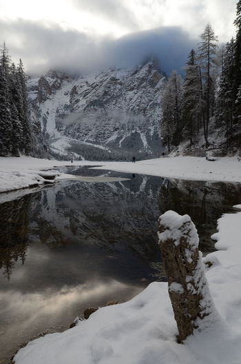 Scenic view of river against cloudy sky during winter