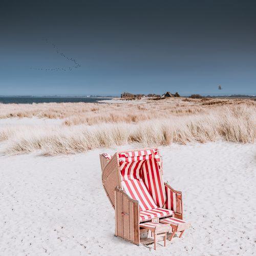 Hooded Beach Chair On Sand Against Clear Sky