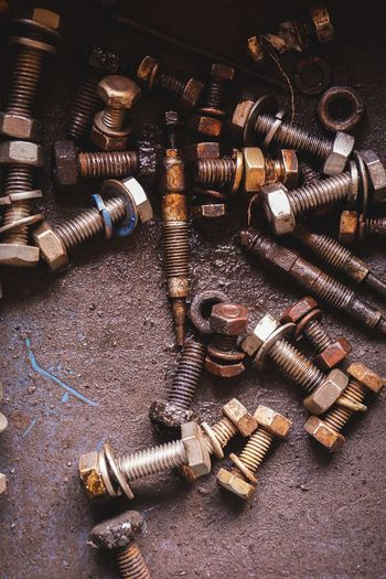 High angle view of old nut and bolts on floor