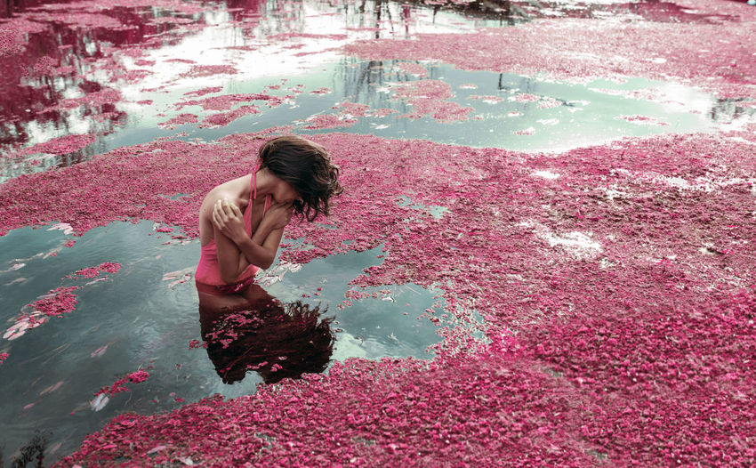 Woman swimming in lake with petals