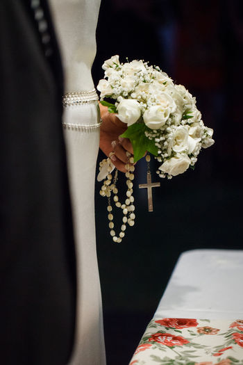 Cropped Image Of Bride Holding Bouquet And Rosary Beads During Wedding Ceremony