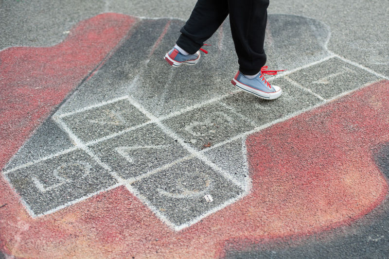 Low section of person playing hopscotch on street