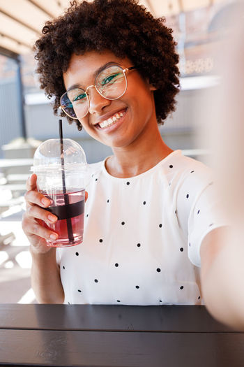 Smiling Portrait One Person Happiness Vlogger Blogger Social Media Girl Woman Selfie Influencer Content Creator  Outdoors Young Lifestyle Cafe Looking At Camera Drink Smartphone Photography Holding Front View