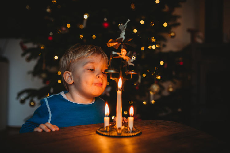 Portrait of boy with illuminated candles on table