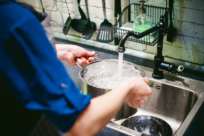 Woman holding container under faucet at kitchen
