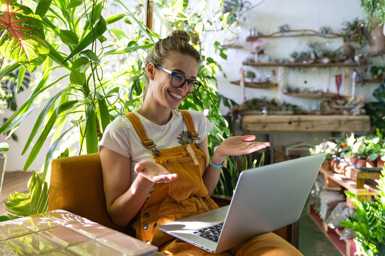Smiling woman video conferencing over laptop while sitting amidst plants at home