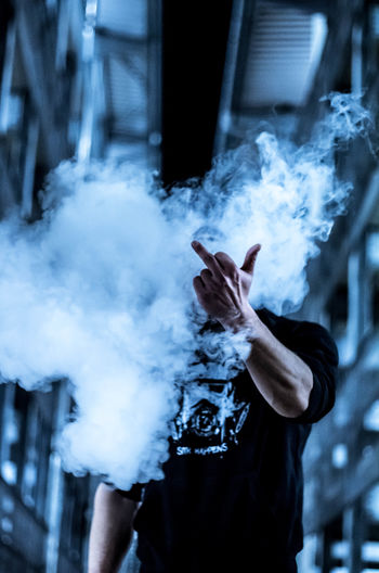 Close-up of man showing obscene gesture through smoke at night