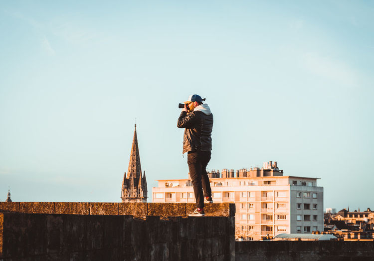 Man photographing while standing on retaining wall against clear sky