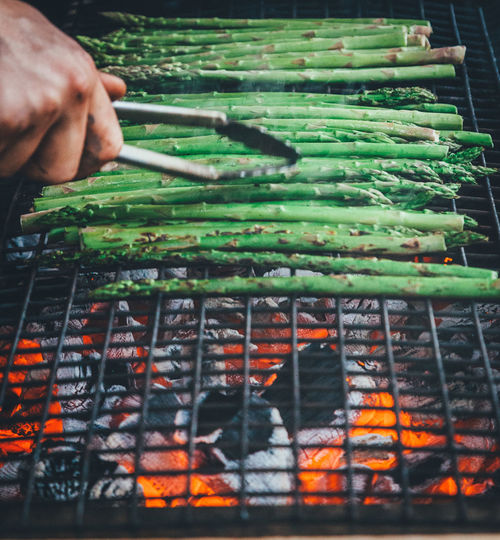 Cropped Hand Of Person Preparing Asparagus On Barbecue Grill